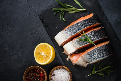 Raw salmon steak on black top view