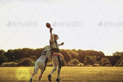 Football player getting tackled during a pass reception