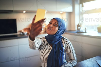 Smiling Arabic woman making faces while taking selfies at home