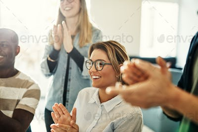 Smiling group of diverse colleagues clapping during an office meeting