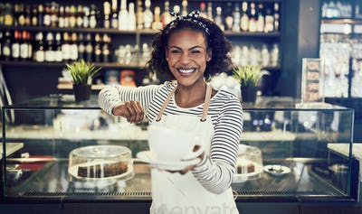 Smiling cafe server offering up a cup of coffee