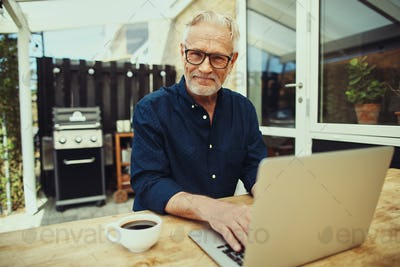 Smiling senior man enjoying a coffee and working online outside