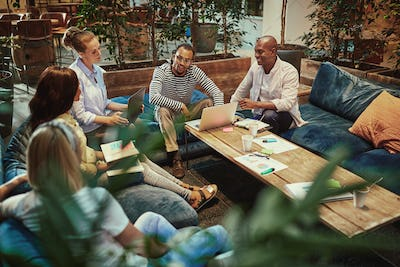 Diverse young businesspeople meeting around a coffee table at work