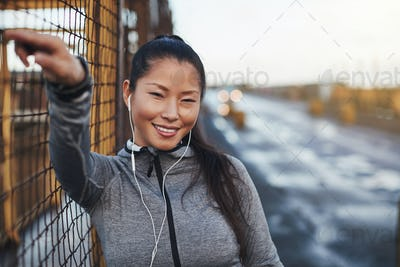 Fit Asian woman listening to music on earphones before running