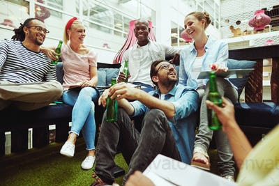 Businesspeople laughing over drinks after work in an office lounge