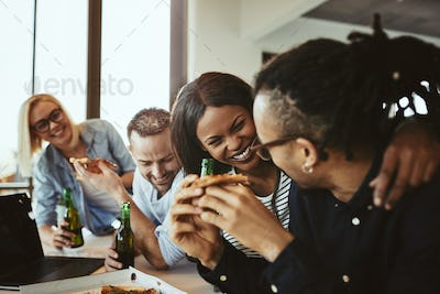 Diverse group of laughing businesspeople having pizza and beer together