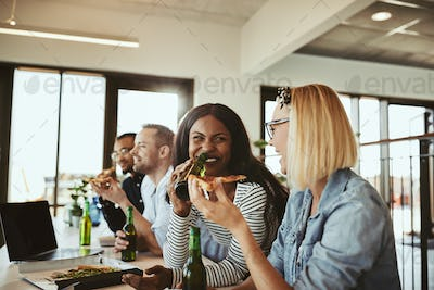 Laughing businesswomen having beer and pizza with colleagues after work