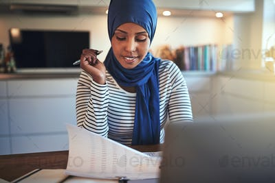 Young Arabic entrepreneur reading documents while sitting in her kitchen