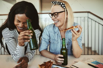 Laughing young businesswomen drinking beers and having pizza after work