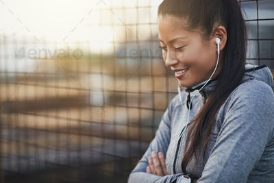 Smiling Asian woman in sportswear standing outdoors listening to music