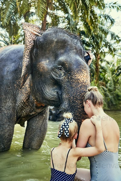 Mother and daughter washing an Asian elephant in a river