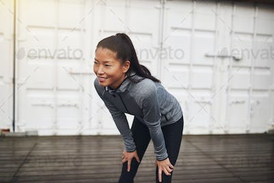 Young Asian woman taking a break from her run