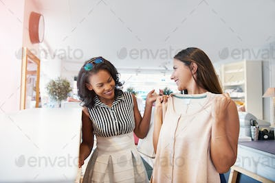 Woman sizing up a dress as friend looks on