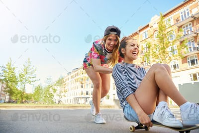 Two laughing young women playing with a skateboard
