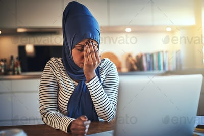 Young Arabic female entrepreneur looking stressed while working from home