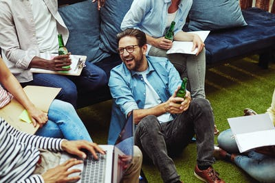 Laughing businesspeople enjoying drinks together after work