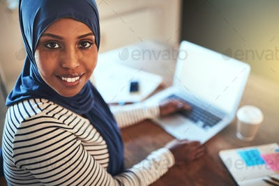 Smiling Arabic female entrepreneur working online with a laptop