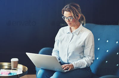 Young woman working online while sitting on a sofa