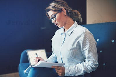 Young businesswoman sitting on a sofa going through paperwork
