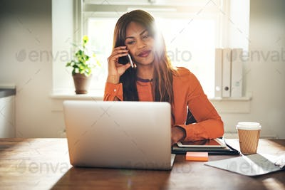 Smiling entrepreneur working from home and talking on a cellphone