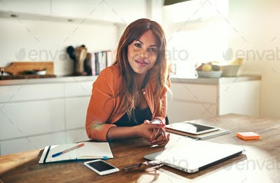 Confident young female entrepreneur working at her kitchen table