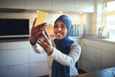 Smiling young Arabic woman taking a selfie in her kitchen