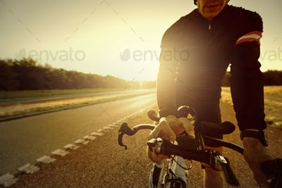 The cyclist riding a bike on highway