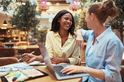 Diverse businesswomen smiling while working together in a lounge