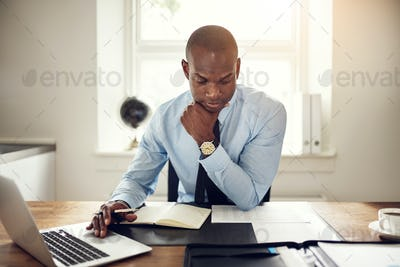 Young businessman hard at work at his office desk