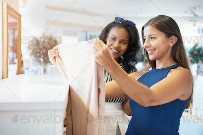 Two young female friends choosing clothes