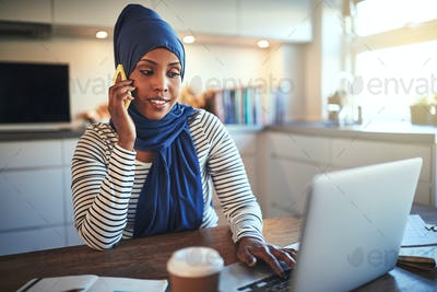 Smiling Arabic female entrepreneur talking on a cellphone at home