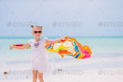 Happy little girl having fun running with pareo on tropical white beach