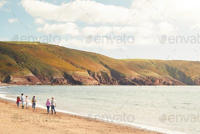 Rear Wide Angle View Of Multi-Generation Family Walking Along Shore On Winter Beach Vacation