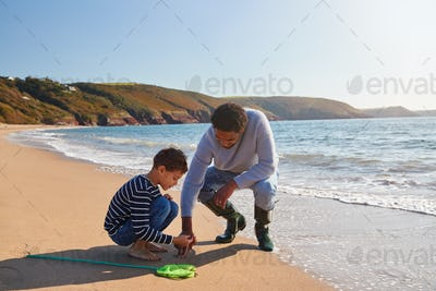 Father And Son Walking Along Beach By Breaking Waves On Beach With Fishing Net Finding Seaweed