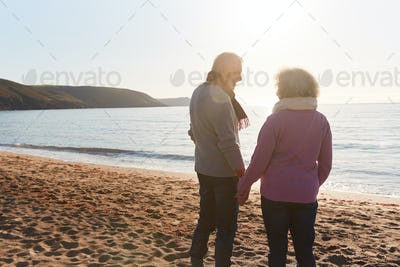 Rear View Of Loving Retired Couple Holding Hands Standing By Shore On Winter Beach Vacation