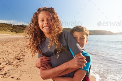 Portrait Of Two Children Wearing Wetsuits Standing By Waves On Summer Beach Vacation