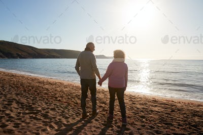Rear View Of Loving Retired Couple Holding Hands Looking Out To Sea On Winter Beach Vacation