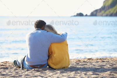 Rear View Of Loving Couple Hugging As They Sit On Sand By Shoreline On Winter Beach Vacation