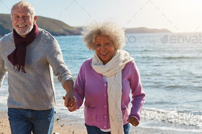 Active Senior Couple Running Along Winter Beach By Waves Holding Hands