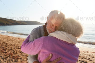 Loving Retired Couple Hugging Standing By Shore On Winter Beach Vacation Against Flaring Sun