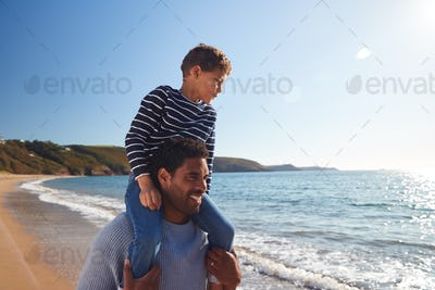 Loving Father Giving Son Ride On Shoulders As They Walk Along Beach Together