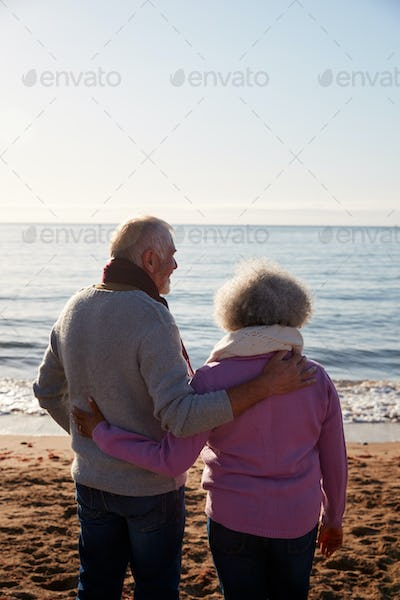 Rear View Of Loving Retired Couple Hugging Standing Looking Out To Sea On Winter Beach Vacation