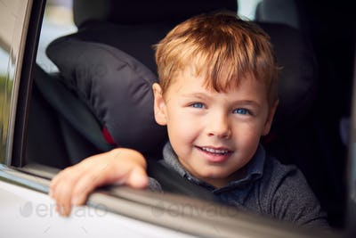 Portrait Of Young Boy Sitting In Child Safety Seat On Car Journey Looking Out Of Window