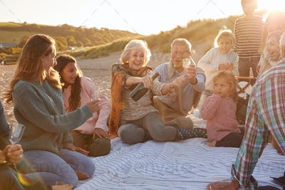 Multi-Generation Family Opening And Pouring Champagne To Celebrate At Winter Beach Vacation
