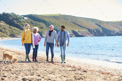 Senior Couple Hold Hands Walking Along Shoreline With Adult Offspring