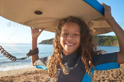 Portrait Of Smiling Girl Wearing Wetsuit Carrying Bodyboards On  Summer Beach Vacation