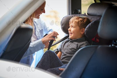 Mother Securing Son Into Rear Child Seat Before Car Journey