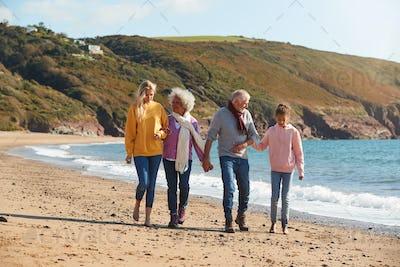 Multi-Generation Family Walking Along Shore On Winter Beach Vacation