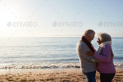 Profile View Of Loving Retired Couple Hugging Standing By Sea On Winter Beach Vacation