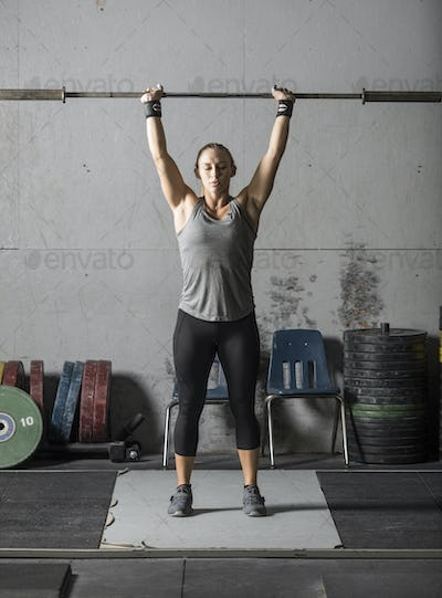 Young woman warming up and getting ready for heavy lifting in gym.